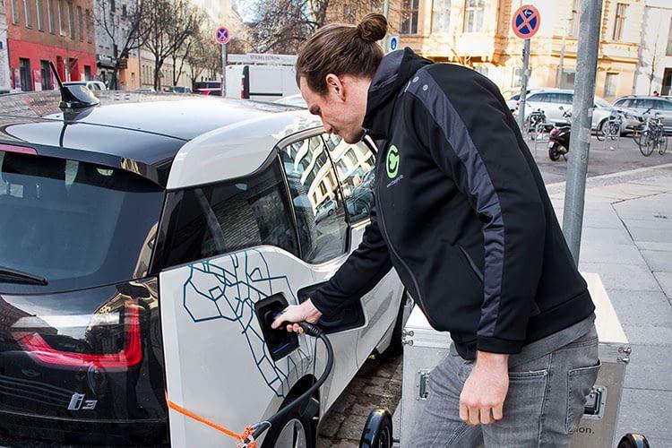 Der Chargery-Mitarbeiter schließt die mobile Powerbank ans Elektroauto an und kümmert sich dann um den nächsten Kunden