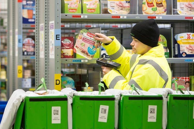 Mitarbeiter verpacken die Bestellungen manuell in Papiertüten