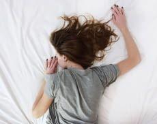 Frau schläft auf weißem Bett